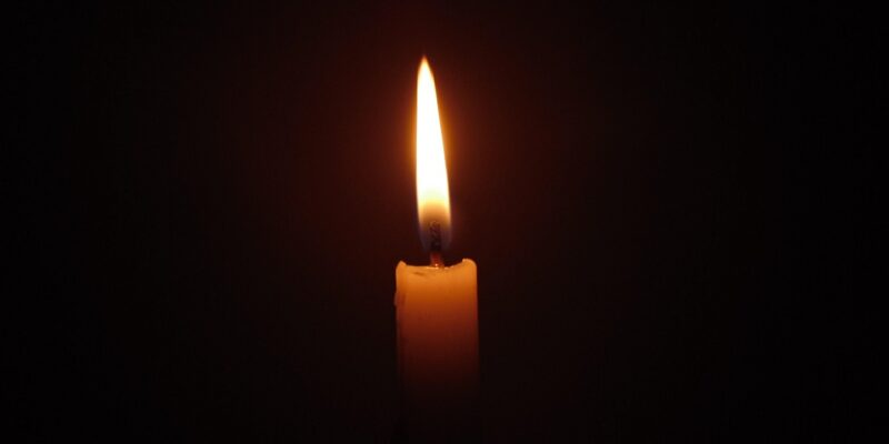 Single burning candle in darkness