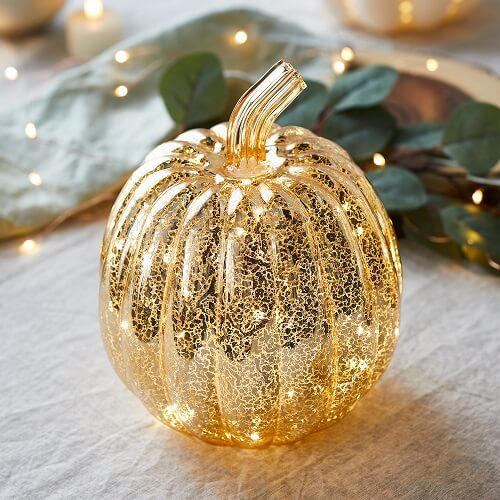Gold glass pumpkin light on table