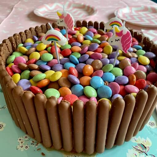 Chocolate cake with rainbow and unicorn candles, smarties and chocolate finger decorations