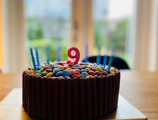 Chocolate birthday cake with candles, decorated with chocolate fingers and smarties