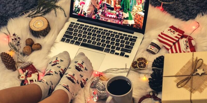 Laptop with feet in snowman socks and Christmas ornaments
