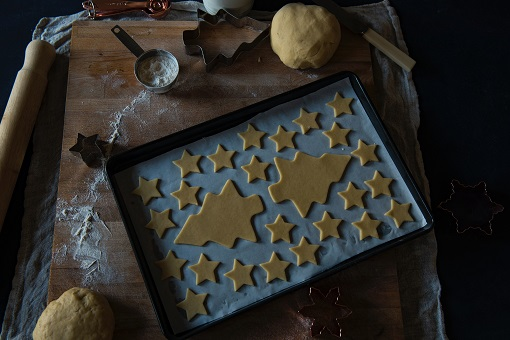 Christmas tree and star cookies on baking sheet
