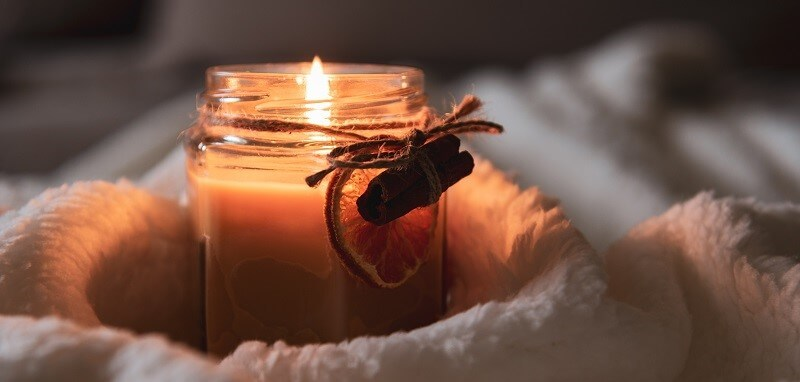 Candle burning in jar with orange and cinnamon decorations