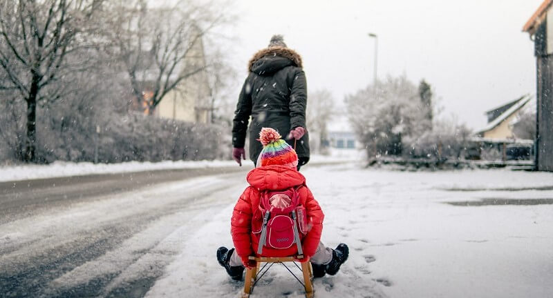 Child being pulled through snow on sled