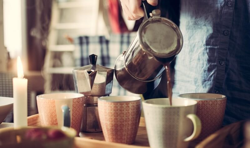 Coffee being poured into mugs