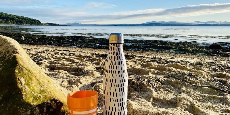 Flask in the sand on a beach