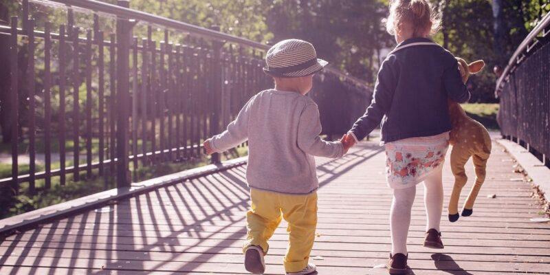 Two children crossing footbridge in park
