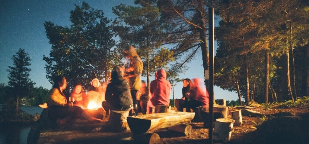 Hygge with others - gathering around campfire